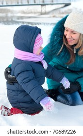 Mother and  kid having fun outdoors on beautiful winter day