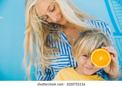 Mother with kid holding oranges