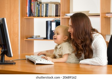 Mother with kid looking computer monitor in office