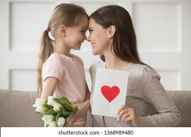 Mother and kid looks at eyes touch foreheads mom express gratitude for gift, daughter congratulate loving mum 8 march holiday presents her white tulips post card with drawn red heart as symbol of love