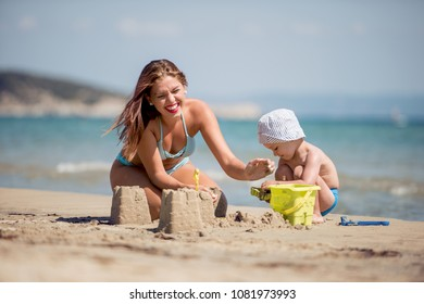 Mother and kid making castles of sand at tropical beach and having fun.