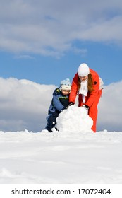 Mother with kid making snowman in winter park