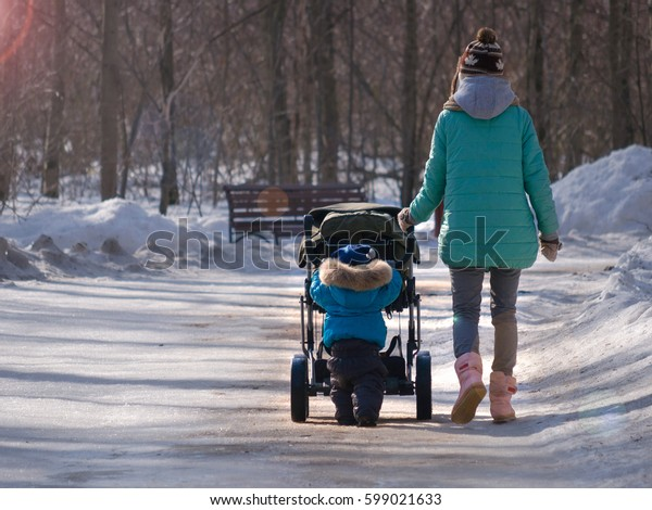 A mother with a kid on a forest walk
