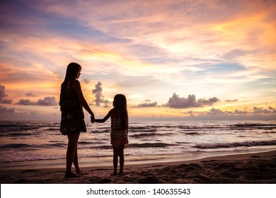 Mother and kid silhouettes on sunset beach
