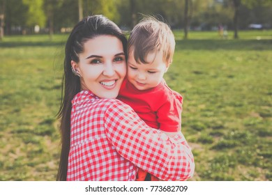 mother with kid smiling in the park. hipster style. casual clothes. concept of happy family