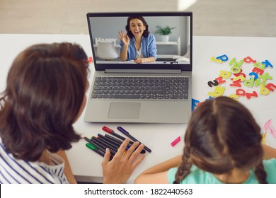 Mother and kid staying at home and E-learning via interactive private school platform. High angle back view mom and daughter video calling tutor on laptop or having online lesson with English teacher
