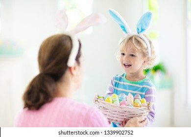 Mother and kids color Easter eggs. Little boy with bunny ears showing mom colorful candy eggs after Easter egg hunt. Family celebration and home decoration for spring holiday.