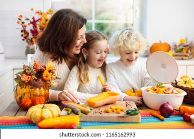 Mother and kids cutting pumpkin, onion and carrot, cooking soup for autumn meal. Mom and children cook healthy fall vegetables for family Halloween season lunch. Boy and girl cut squash in kitchen.