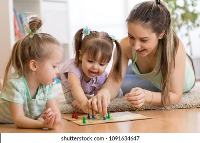 Mother and kids daughters sitting in a playroom, playing a ludo game and enjoying their time together
