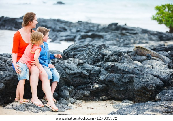 Mother and kids looking at endemic marine iguana at Galapagos islands