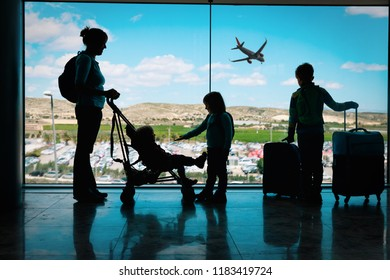 mother with kids and luggage looking at planes in airport