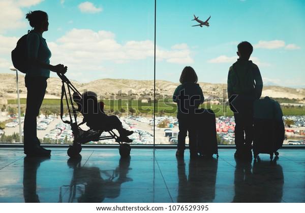 Mutter mit Kindern und Gepäck, die Flugzeuge am Flughafen ansieht