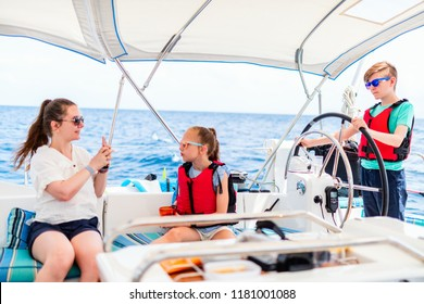 Mother and kids on board of sailing yacht having summer travel adventure