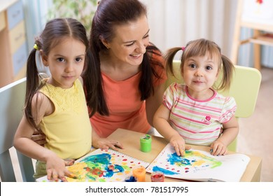 Mother and kids are painting together. Happy family are coloring with paintbrush. Woman and children have a fun pastime.