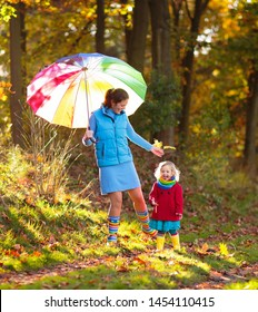 Mother and kids play in autumn park. Mom and child with umbrella and rain boots play outdoors in rain. Little girl playing in puddle. Family fun by rainy fall weather. Children outdoor. Kid in forest.