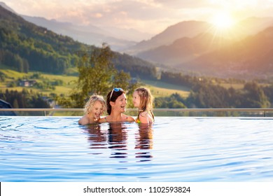 Mother and kids play in outdoor infinity swimming pool of luxury spa alpine resort in Alps mountains, Austria. Spring or summer vacation for family with children. Kids in hot tub with mountain view.