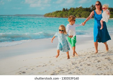 mother with kids play run on tropical beach