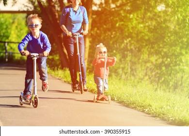 mother with kids riding scooters in summer