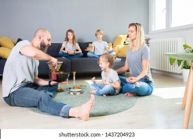 Mother and kids sitting in pose of lotus with their eyes closed and meditating, Sound meditation.Relaxed and peaceful family is meditating while father helps them playing on Tibetan singing bowl