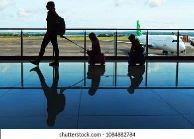 Mother with kids walk to flight boarding in airport transit hall and look through the window at airplane near departure gate. Active family lifestyle, travel by plane with children on summer vacation.
