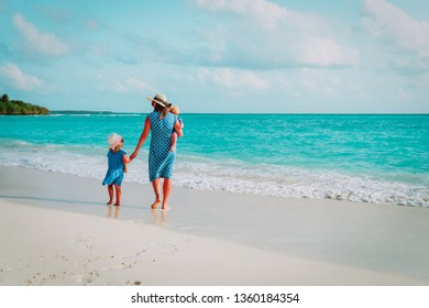 mother with kids walk on beach, family vacation