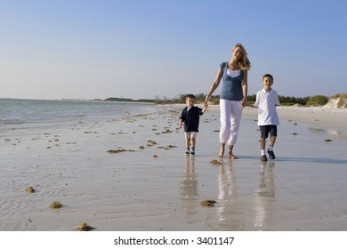 Mother and kids walking on a beach.  Ocean in the background.