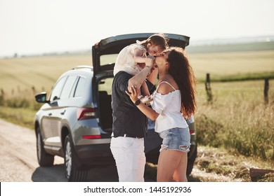 Mother kisses daughter. Family have some good time at countryside near silver automobile at sunset.