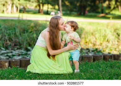 Mother kisses daughter in park on green lawn