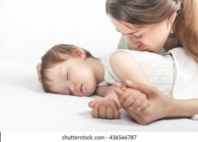 Mother kissing a baby. Care concept. Protection. Healthy sleep. Healthcare. Medical. Mother's care is most important in baby live. White background