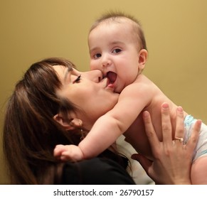 a mother kissing a child