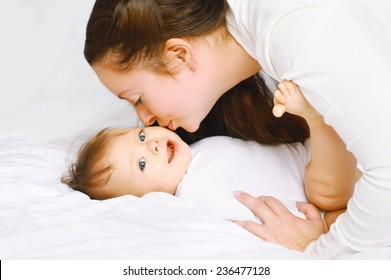 Mother kissing cute baby on the bed at home