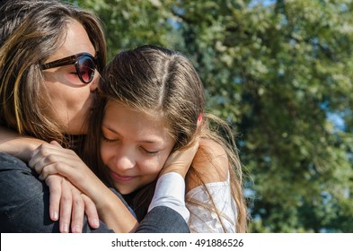 Mother kissing daughte, hugging in the park
