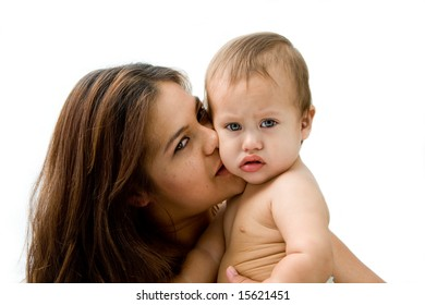 Mother kissing her baby boy who's looking naughty, isolated