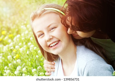 Mother kissing her daughter at sunny day