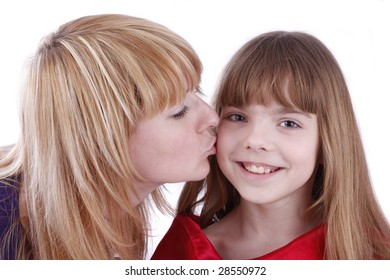 Mother is kissing her happy daughter. Mother's kiss. Isolated on white in studio.