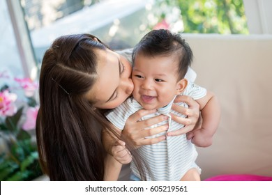 Mother kissing her little boy on the cheek in home