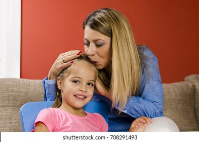Mother kissing her little girl in the head with closed eyes, closeup portrait