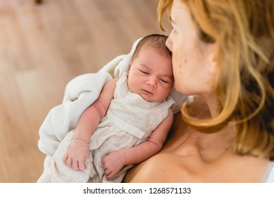 Mother kissing her newborn daughter after breastfeeding