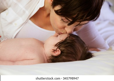 Mother kissing newborn on changing table