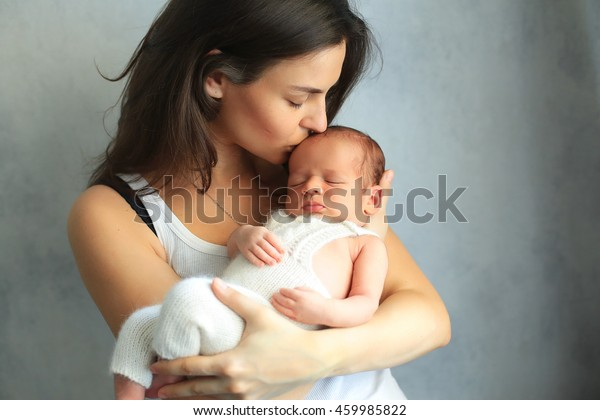 Mother kissing newborn son at grey background. Portrait of woman and little baby