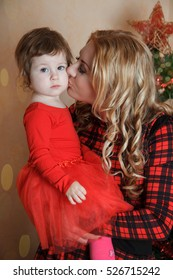 Mother kissing small daughter under Christmas tree