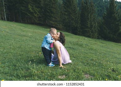 mother kissing son with bottle on meadow