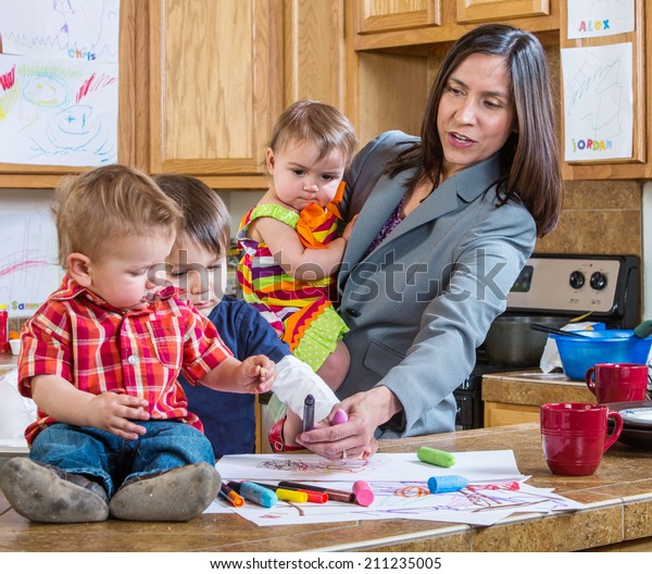 A mother in the kitchen plays with her children
