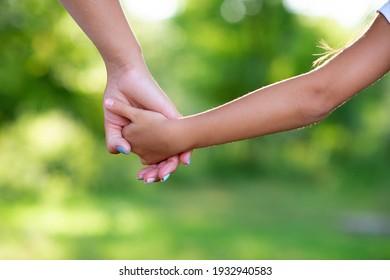 Mutter führt ihr Kind in der Natur des Sommers Waldes im Freien. Konzept des Vertrauens, der Familie, des Schutzes und der Hilfe. Weibliche und kinderreiche Hände, Nahaufnahme vor dem Hintergrund der Sommerlandschaft.