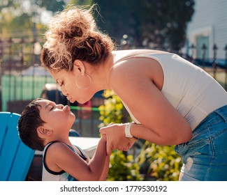 A mother is leaning to kiss her son on the lips at a backyard pool party