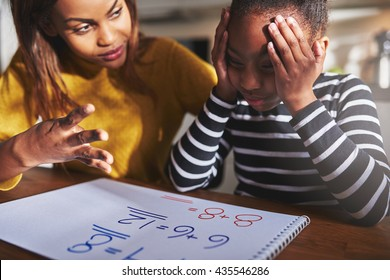 Mother learning child to calculate, child looking frustrated. Black woman and child