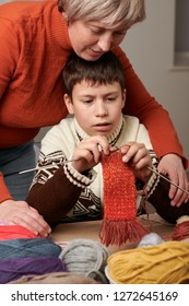 Mother is learning her child boy to knit. Colorful wool yarns are on the wooden table.