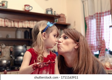 A mother letting her daughter make a mass with flour and fruit jam while on the kitchen's table, kissing her as a sign of love.