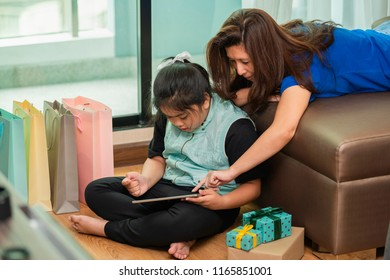 Mother and Little Asian girl watching tablet learning and playing tablet.