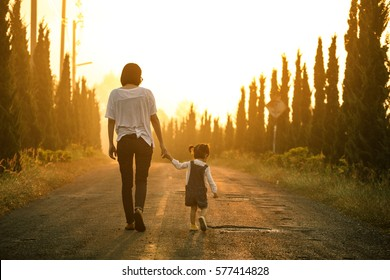 Mother and little asian toddler girl walking together on the way at the sunset with copy space, New family and baby protection from mom concept